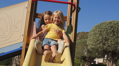Slow motion of two children on slide in park. - stock footage
