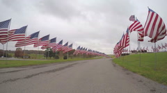 Super slow motion drive through of American flags memorial Stock Footage