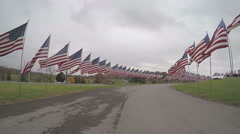 Slow motion drive through a Veterans Memorial of USA flags Stock Footage