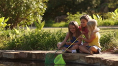 Three children playing with fishing nets by pond in park. Stock Footage