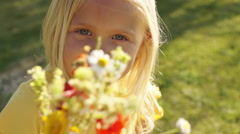 Portrait of one child with bunch of wild flowers in park. Stock Footage