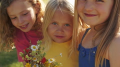 Portrait of three children with bunch of wild flowers in park. Stock Footage