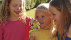 Portrait of three children licking lollypop in park. Stock Footage