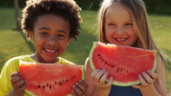Two children eating water melon in park. - stock footage