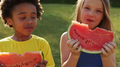 Two children eating water melon in park. Stock Footage