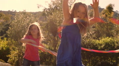 Slow motion of two children playing with hula hoop in park. - stock footage