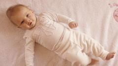 Overhead shot of young baby lying on back. Stock Footage