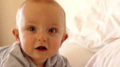 12 month old baby  playing on bed indoors. - stock footage