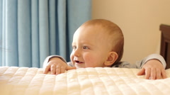 Mother and 12 month old baby  playing on bed indoors. Stock Footage