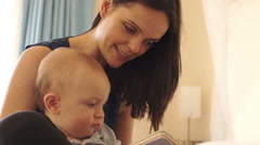Mother and 12 month old baby  reading on bed indoors. - stock footage