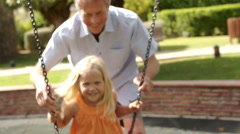 Slow motion of grandfather pushing granddaughter on swing in park. Stock Footage