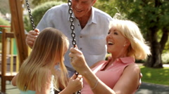 Grandfather pushing grandmother and granddaughter on swing in park. - stock footage