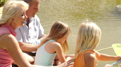 Grandparents and two granddaughters fishing with net in pond in park. Stock Footage