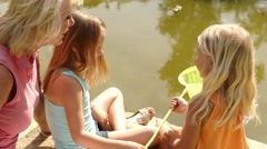 Grandmother and two granddaughters fishing with net in pond in park. - stock footage