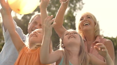 Grandparents and two granddaughters playing with balloons in park. Stock Footage