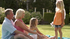 Grandparents and two granddaughters playing in park with magic wand. Stock Footage