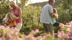 Slow motion of grandparents and grandchildren twirling around in park. Stock Footage