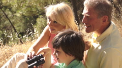 Senior couple and grandchild sitting in countryside enjoying views with Stock Footage