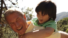 Slow motion of grandfather with playing with grandson on his back. - stock footage