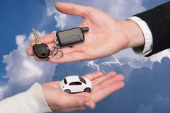 man holding small car key, woman holding small car - stock photo