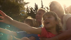Slow motion of grandchildren and grandparents in garden playing with bubbles. Stock Footage