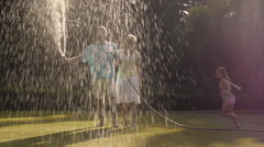 Grandchildren and grandparents in garden playing with water spray. Stock Footage