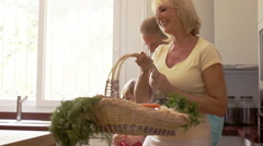 Grandparents and granddaughter in kitchen with fresh vegetables in basket. - stock footage