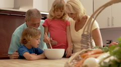 Slow motion of grandparents and grandchildren in kitchen mixing flour in bowl. - stock footage