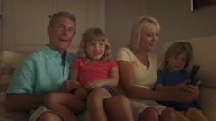 Grandparents and grandchildren in living room watching television on sofa. Stock Footage