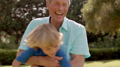 Grandfather playing with grandson in garden, swinging him around. Stock Footage