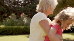 Grandmother playing with granddaughter in garden, swinging her around. - stock footage