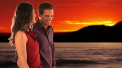 Dolly shot of mid aged couple walking in sunset Stock Footage