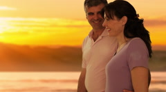 dolly shot of mid aged couple walking in sunset - stock footage