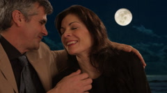 Mid aged couple sitting in moonlight Stock Footage