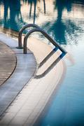 Aluminium steps at the edge of a swimming pool Stock Photos