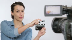 Stage director enter production set with clapper Stock Footage