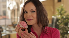 Stock Video Footage of young girl eating cupcake in town