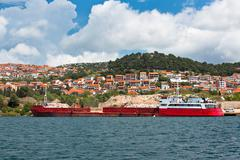 Bulk carrier with cargo near a river coast Stock Photos