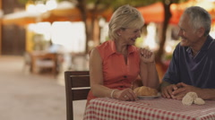 Dolly shot of senior couple at cafe in town waiter bringing coffee Stock Footage