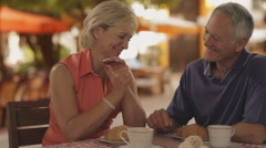 zoom in shot of senior couple at cafe in town - stock footage