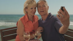 Senior couple at beach cafe by sea taking picture Stock Footage