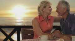 Dolly shot of senior couple at beach cafe in sunset Stock Footage