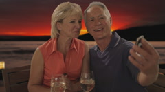 Senior couple taking picture at beach cafe in sunset Stock Footage
