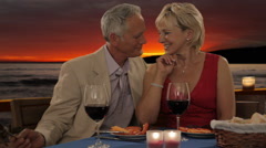 Dolly shot of senior couple at dinner in sunset giving rose Stock Footage