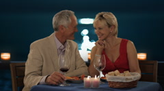 Senior couple in moonlight having dinner waiter pouring wine Stock Footage