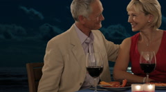 Dolly shot of senior couple in moonlight giving present of rose Stock Footage