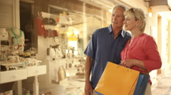 Senior couple looking in shop window in town Stock Footage