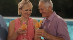 zoom in shot of senior couple relaxing by poolside with drinks - stock footage
