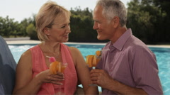 senior couple relaxing by poolside with drinks - stock footage
