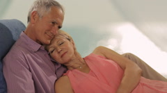 Zoom in shot of senior couple relaxing by sea Stock Footage